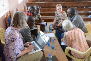 Kenyans and Americans gather around a table to collaborate
